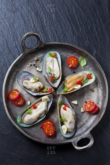 Green mussels with tomatoes- capsicum and garlic- in iron pan