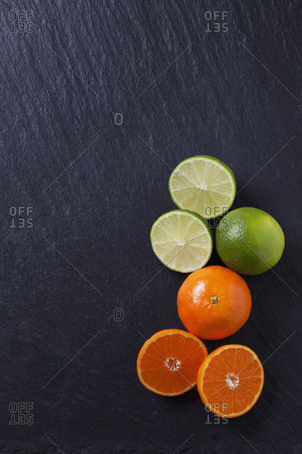 Limes and tangerines on black slate slab