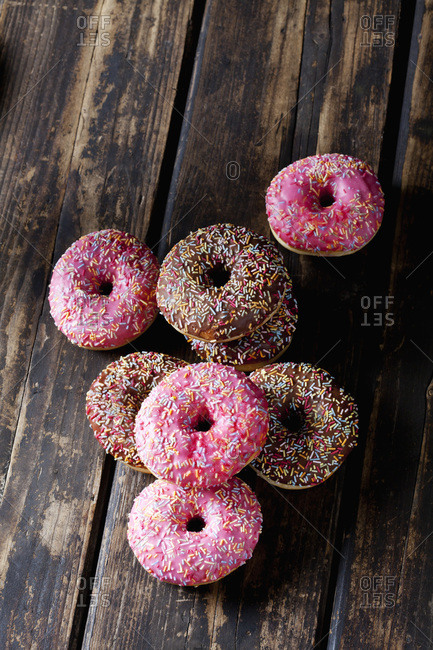 Colorful donuts on wood with sugar sprinkles