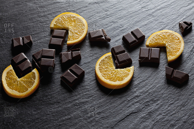 Cocolate pieces with orange slices on black slate