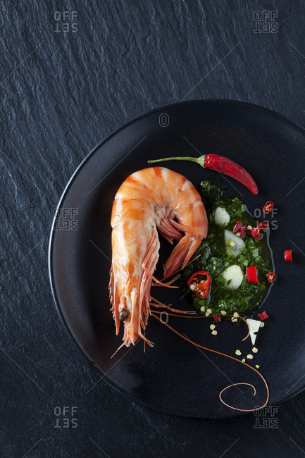 Prawn with hernbs- chili and garlic on black plate