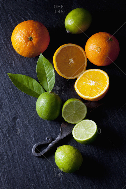Sliced limes and oranges with an old knife