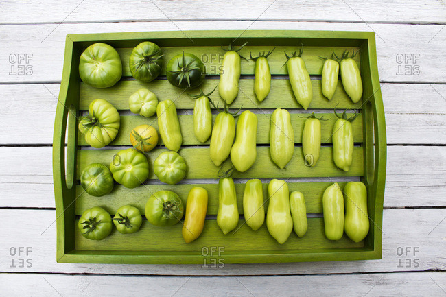 Wooden tray with various tomatoes- stage of ripeness- unripe