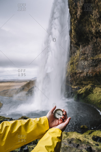 Iceland- Seljalandsfoss Waterfall- woman's hand holding compass