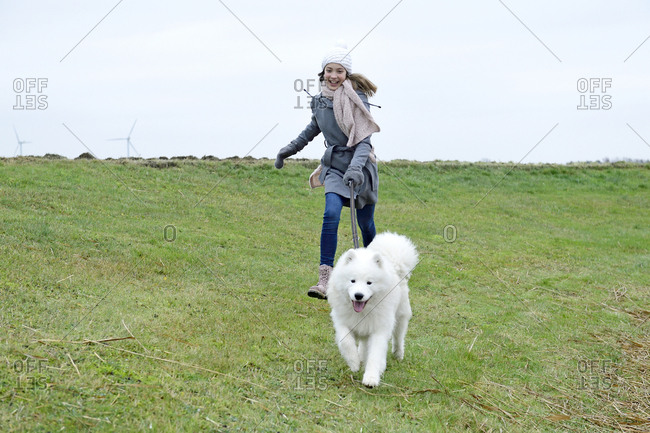 Laughing girl running on a meadow with her dog