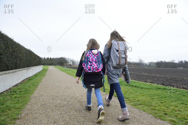 Two sisters with backpacks walking side by side