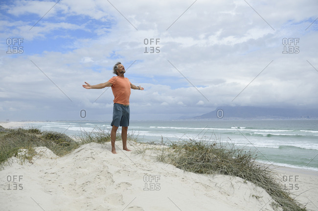 South Africa- man raising arms at Bloubergstrand