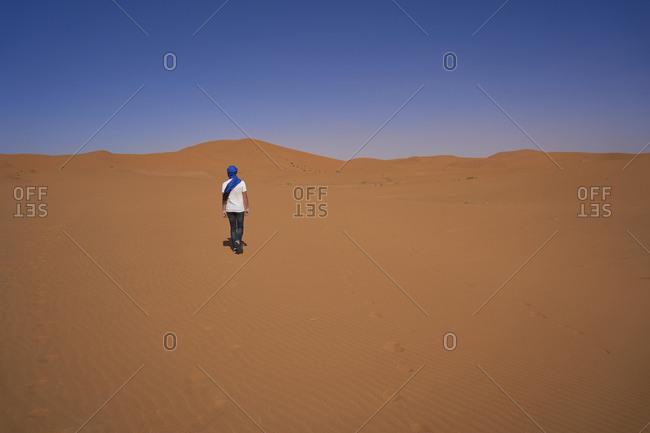 Morocco- back view of man walking on desert dune