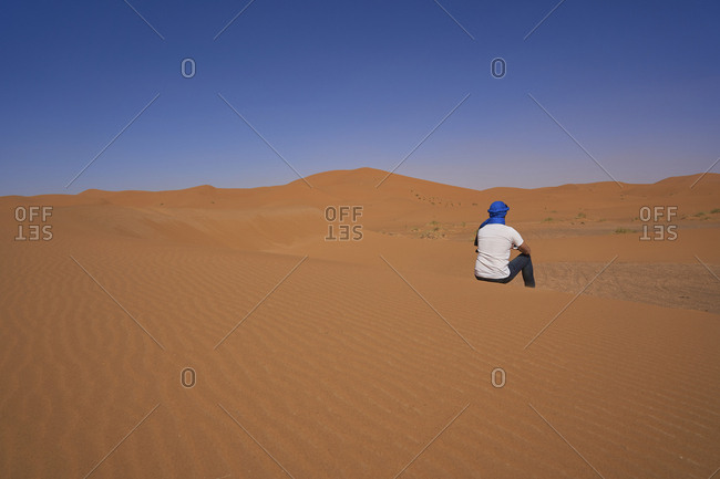 Morocco- back view of man sitting on  desert dune