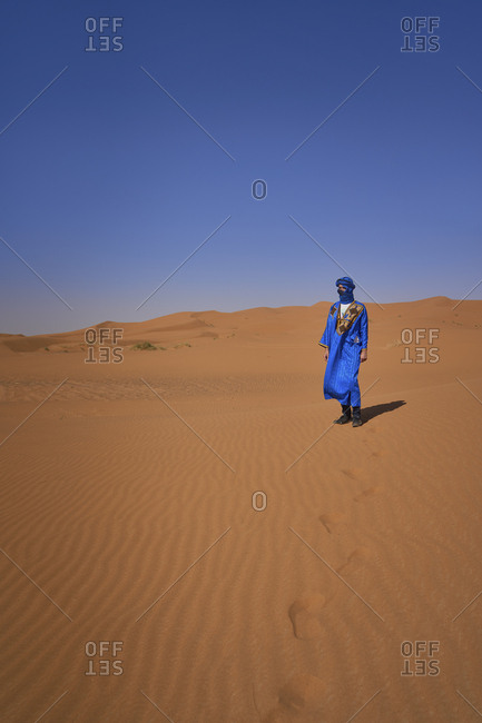 Morocco- man wearing blue kaftan and turban standing on desert dune