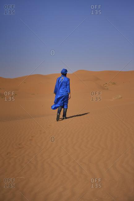 Morocco- back view of man wearing blue kaftan and turban walking on  desert dune