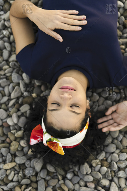 Young woman with closed eyes lying on stones