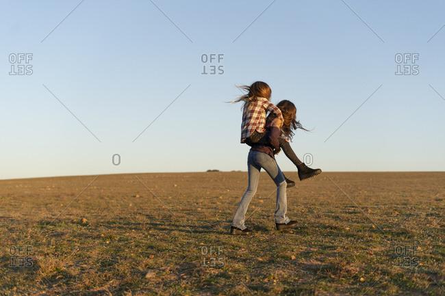 Girl giving her sister a piggyback ride outdoors