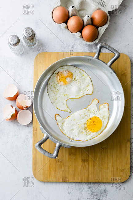 Two fried eggs with pepper in pan