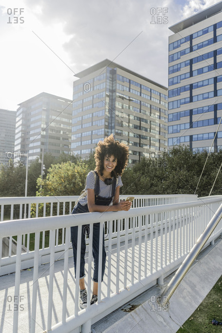 Young woman standing on a bridge- using smartphone- with headphones around her neck