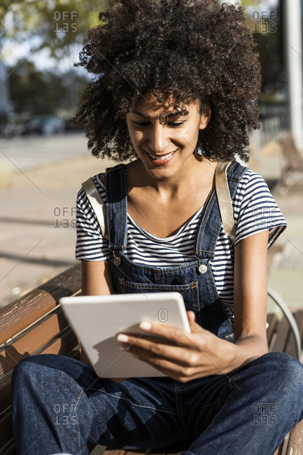 Mid adult woman with curly hair- sitting on a bench- using digital tablet