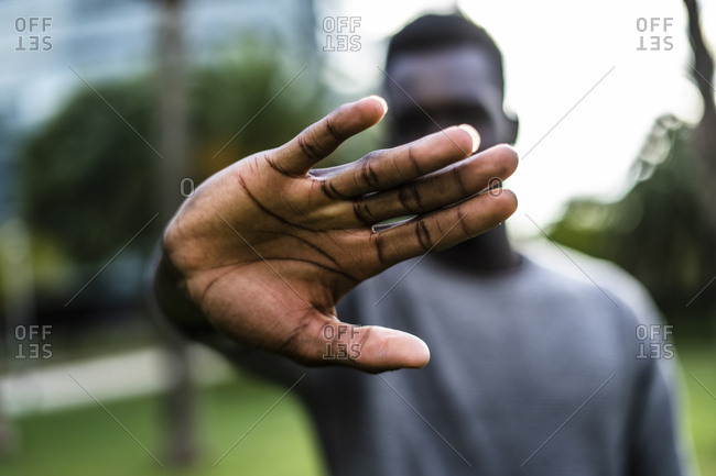 Young man holding hand in front of his face