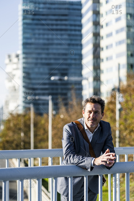 Relaxed businessman leaning on a railing- taking a break