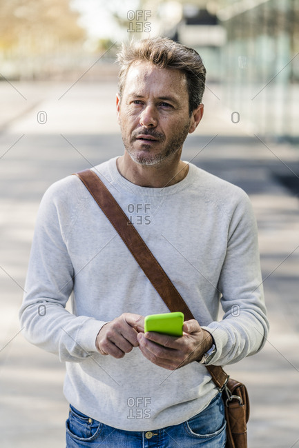 Mature man commuiting in the city- holding smartphone