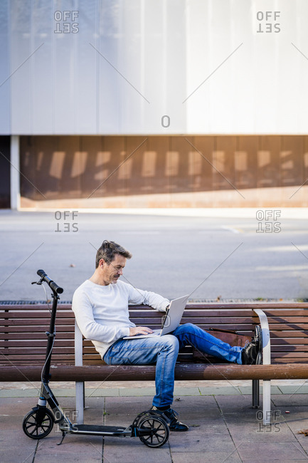 Casual businessman with kick scooter- sitting on a bench- working relaxed in the city