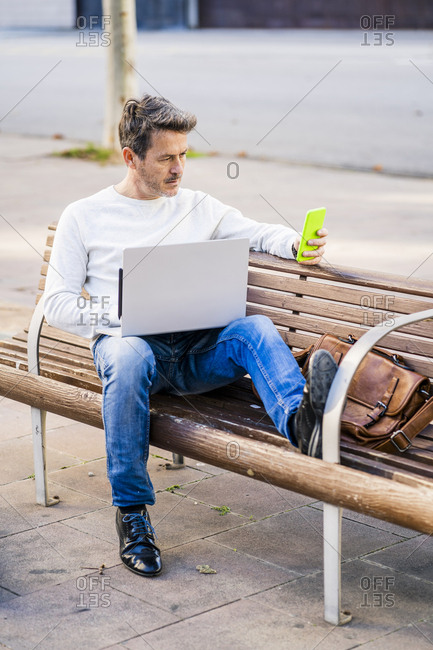 casual businessman sitting on a bench- working relaxed in the city
