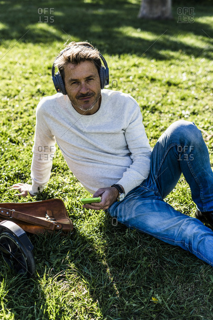 Casual businessman taking a break in a prak- sitting on grass- listening music