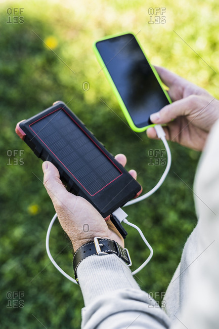 Businessman charging his smartphone with a solar power bank
