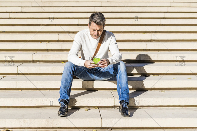 Casual businessman sitting on stairs- reading messages on his smartphone