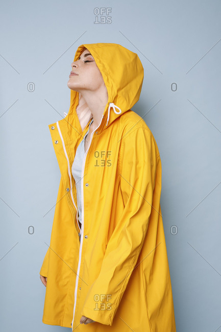 Young woman wearing yellow rain coat in front of blue background
