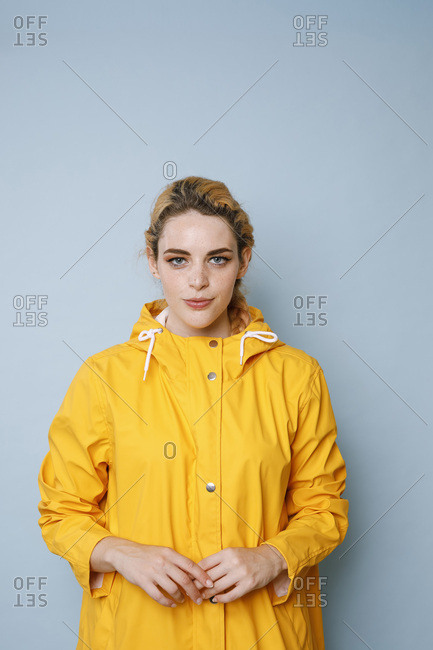 Portrait of young woman wearing yellow rain coat in front of blue background