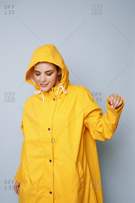 Smiling young woman wearing yellow rain coat in front of blue background dancing
