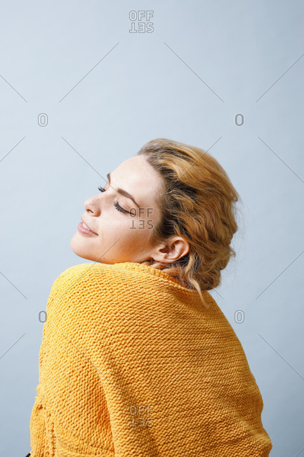 Smiling young woman wearing yellow knitwear in front of blue background