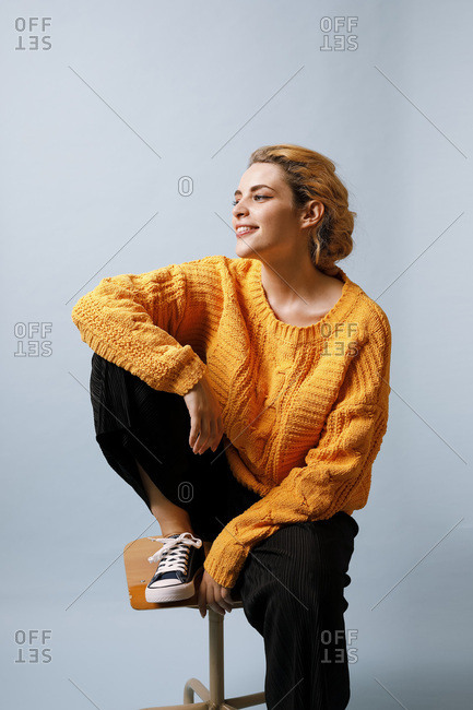 Smiling young woman sitting on chair in front of blue background wearing yellow knit pullover