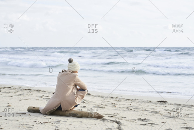 Spain- Menorca- back view of senior woman wearing bobble hat and coat sitting on the beach in winter