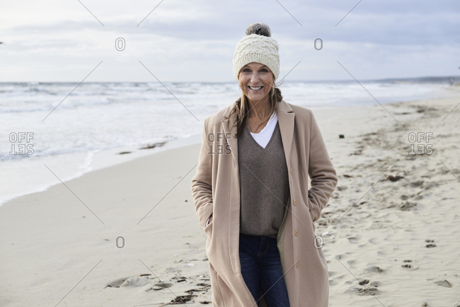 Spain- Menorca- portrait of smiling senior woman wearing bobble hat and coat on the beach in winter