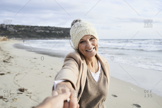 Spain- Menorca- portrait of happy senior woman holding hand on the beach in winter