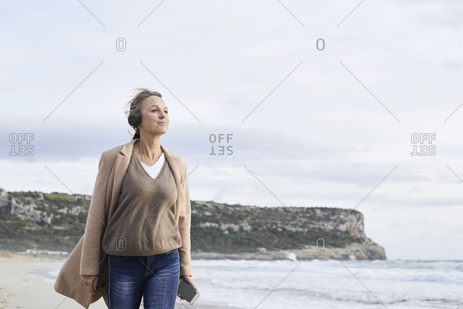Spain- Menorca- senior woman using smartphone and wireless headphones  on the beach in winter
