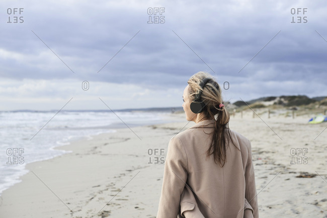 Spain- Menorca- back view of senior woman listening music with wireless headphones on the beach in winter