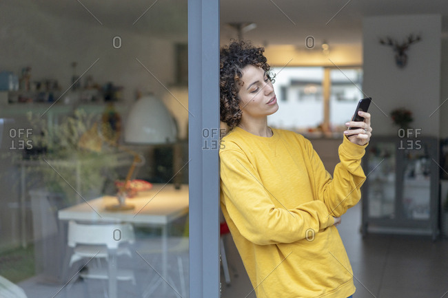 Woman leaning against terrace door at home checking cell phone