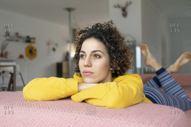 Woman lying on couch at home thinking