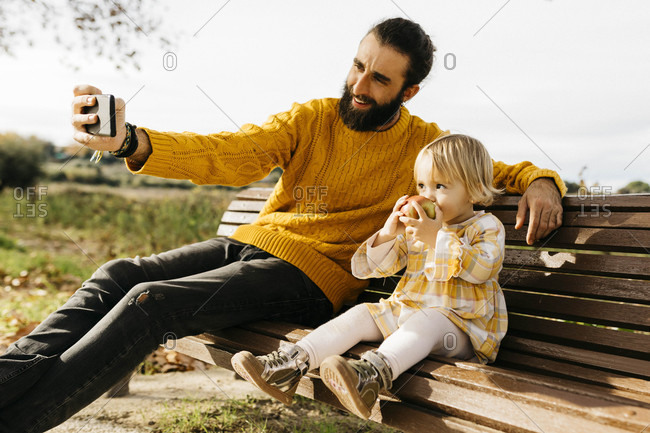 Father and daughter sitting on a bench in the park in autumn- father taking a selfie- daughter eating an apple