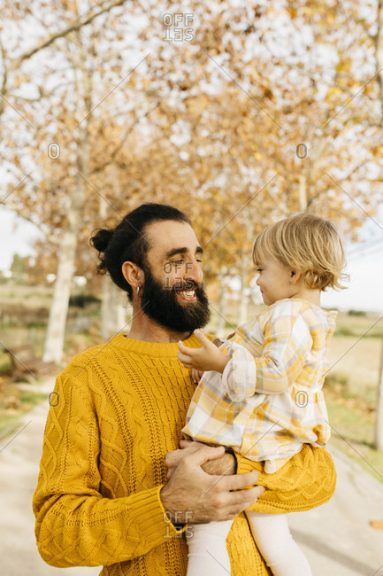 Father carrying his daughter on a morning day in the park in autumn
