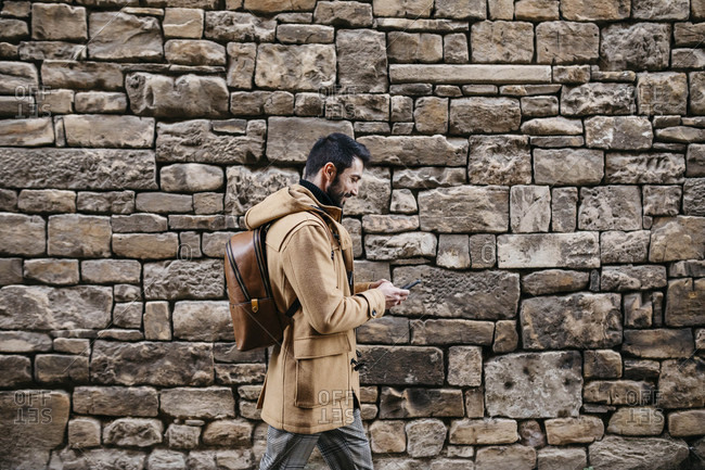 Spain- Igualada- man walking along stone wall using cell phone