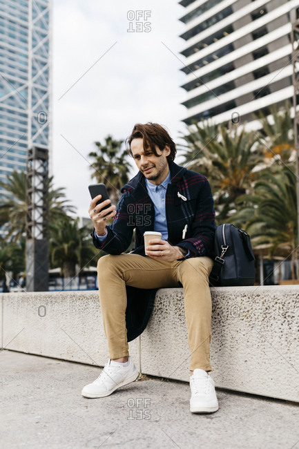 Spain- Barcelona- man sitting in the city with takeaway coffee and cell phone