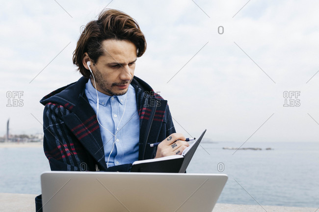 Spain- Barcelona- man sitting at the sea working with laptop and notebook