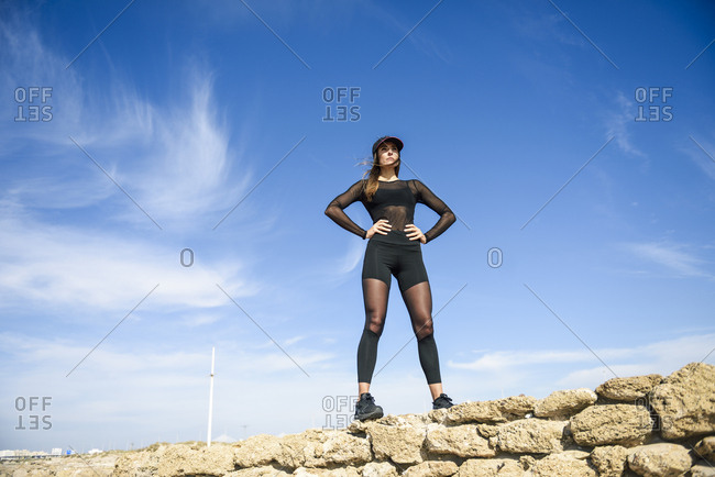 Confident sportive woman standing on stone wall