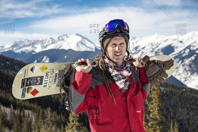 March 15, 2013: USA, Colorado, Aspen, portrait of a snowboarder at the top of the gondola at Aspen Ski Resort, Ajax, the Elk Mountains in the distance