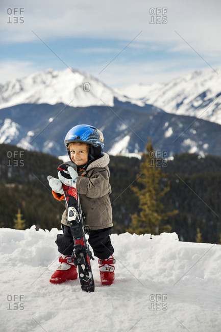 March 15, 2013: USA, Colorado, Aspen, portrait of a young skier at the top of the gondola at Aspen Ski Resort, Ajax, the Elk Mountains in the distance