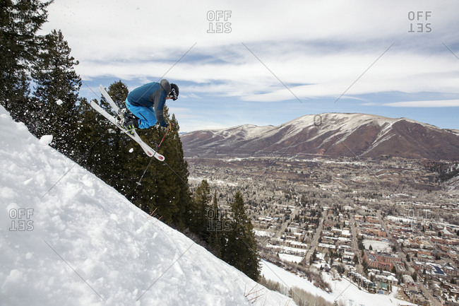 March 15, 2013: USA, Colorado, Aspen, skier getting air on a trail called Corkscrew with the town of Aspen in the distance, Aspen Ski Resort, Ajax mountain