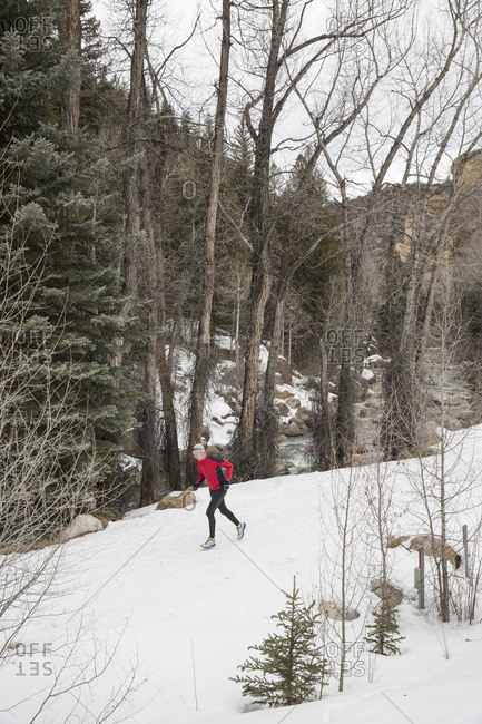 March 18, 2013: USA, Colorado, Aspen, a man runs on the snowy Rio Grande Trail next to the Roaring Fork River, River Gorge section